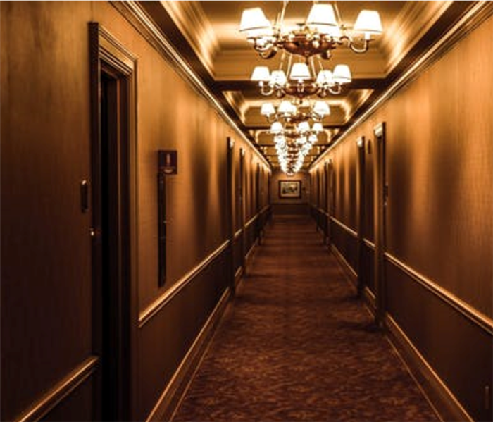 Long dark hallway with chandeliers